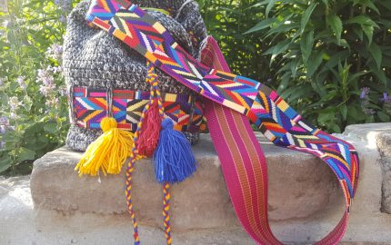 szydełkowa torebka z DMC Denim ozdobiona kolorowymi taśmami ustawiona na murze